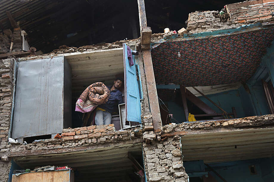 A resident carries his belongings retrieved from the ruins of his home after Saturday's earthquake in Bhaktapur, Nepal, Tuesday, April 28, 2015. Many people have camped outdoors in the chilly night cold since Saturday's massive earthquake that shook Nepal's capital and the densely populated Kathmandu valley. (AP Photo/Bernat Armangue)