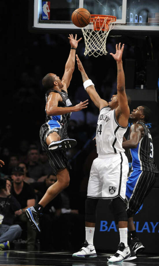 Brooklyn Nets' Paul Pierce (34) blocks the shot of Orlando Magic's Arron Afflalo, left, in the first half of an NBA basketball game Sunday, April 13, 2014, in New York. (AP Photo/Kathy Kmonicek)