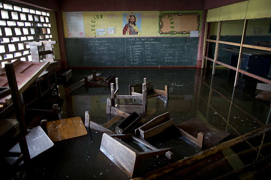 """In this April 20, 2015 photo, benches float in a classroom inside the half-flooded San Jose school due to the rising of the Itaya river in Belen, a neighborhood nicknamed """"Venice of the Jungle"""" in Iquitos, Peru. This """"Amazonian Venice"""" draws a lot of tourists who arrive in boats during the watery season, but the community is a lot less picturesque for the people who live there. (AP Photo/Rodrigo Abd)"""