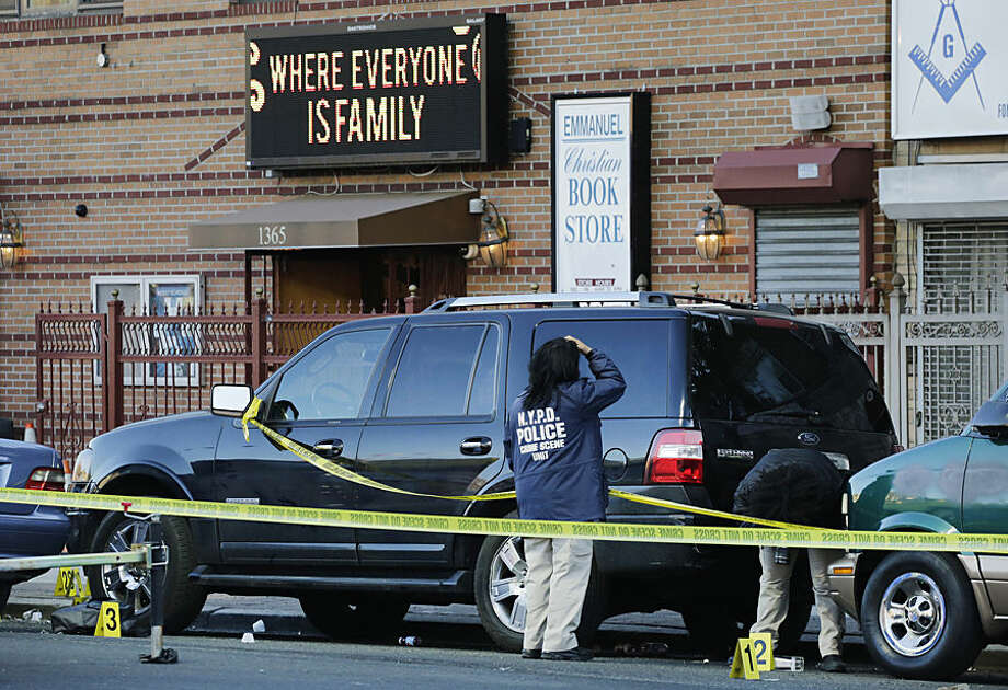 New York Police Department crime scene investigators photograph evidence outside Emmanuel Church of God, Tuesday, April 28, 2015, in the Brooklyn borough of New York. Two men were killed Monday night during a shooting outside the Flatbush neighborhood church where a funeral was taking place. Four other people were injured and are in stable condition. (AP Photo/Mark Lennihan)