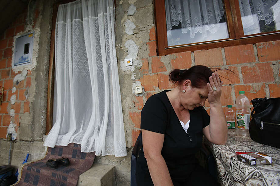 "Bosnian woman Rajfa Cerkic, a family member of Nerdin Ibric the gunmen who attacked a police station, reacts as they gathered in the family house, in the village of Kucic Kula near the eastern Bosnian town of Zvornik, 200 kms east of Sarajevo, Tuesday, April, 28, 2015. Bosnian authorities say a man stormed into a police station in a northeastern town Monday shouting ""Allahu akbar,"" killing a policeman and wounding two others. (AP Photo/Amel Emric)"