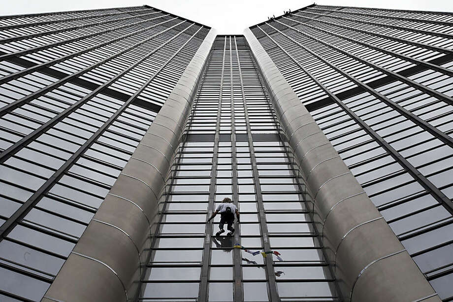 Alain Robert, also known as the French Spiderman, climbs the Montparnasse tower a 210-metre (689 ft) office skyscraper located in the Montparnasse area of Paris, France, Tuesday, April 28, 2015. Robert decided to climb in solidarity with the victims of the Saturday's earthquake in Nepal. (AP Photo/Christophe Ena)