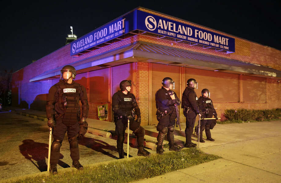 Police stand outside a shuttered store, Monday, April 27, 2015, during unrest following the funeral of Freddie Gray in Baltimore. Rioters plunged part of Baltimore, torching a pharmacy, setting police cars ablaze and throwing bricks at officers. (AP Photo/Patrick Semansky)