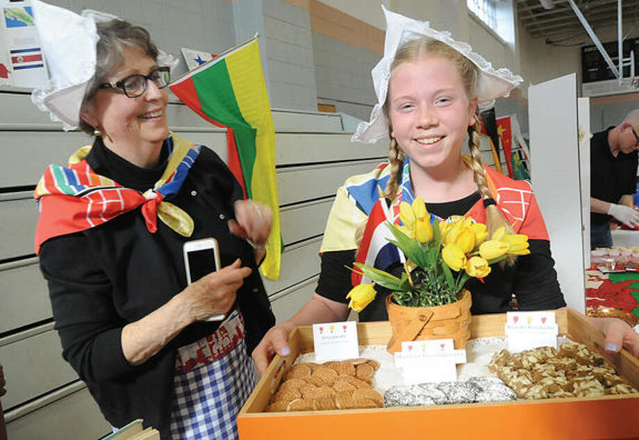 Meghan Burke All Saints 8th grader with her grandmother Camille Vandermeulen with Dutch Cookies at the School's international Night. Hour photo/Matthew Vinci