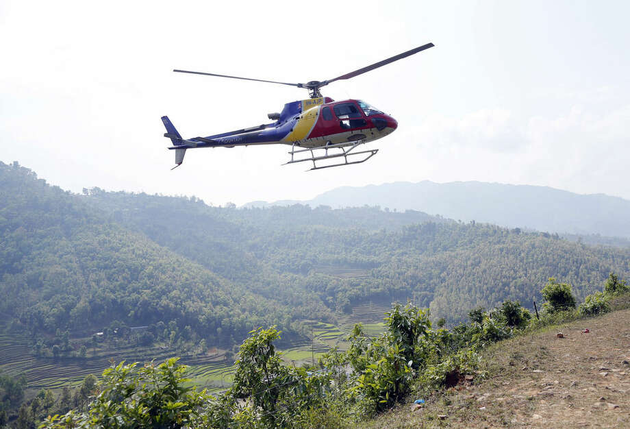 A helicopter carrying supplies and officials lands at a relief staging area near Saturday's massive earthquake's epicenter in the town of Gorkha, Nepal, Tuesday, April 28, 2015. Preparing to make a push into the most isolated parts of quake-devastated Nepal, soldiers on Tuesday were readying food, water and other emergency supplies to be loaded onto helicopters in this small town near the earthquake's epicenter. (AP Photo/Wally Santana)