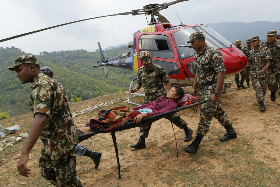 Sita Karka, suffering two broken legs from Saturday's massive earthquake, arrives by helicopter from the heavily-damaged Ranachour village at a landing zone in the town of Gorkha, Nepal, Tuesday, April 28, 2015. Helicopters crisscrossed the skies above the high mountains of Gorkha district on Tuesday near the epicenter of the weekend earthquake, ferrying the injured to clinics, and taking emergency supplies back to remote villages devastated by the disaster. (AP Photo/Wally Santana)