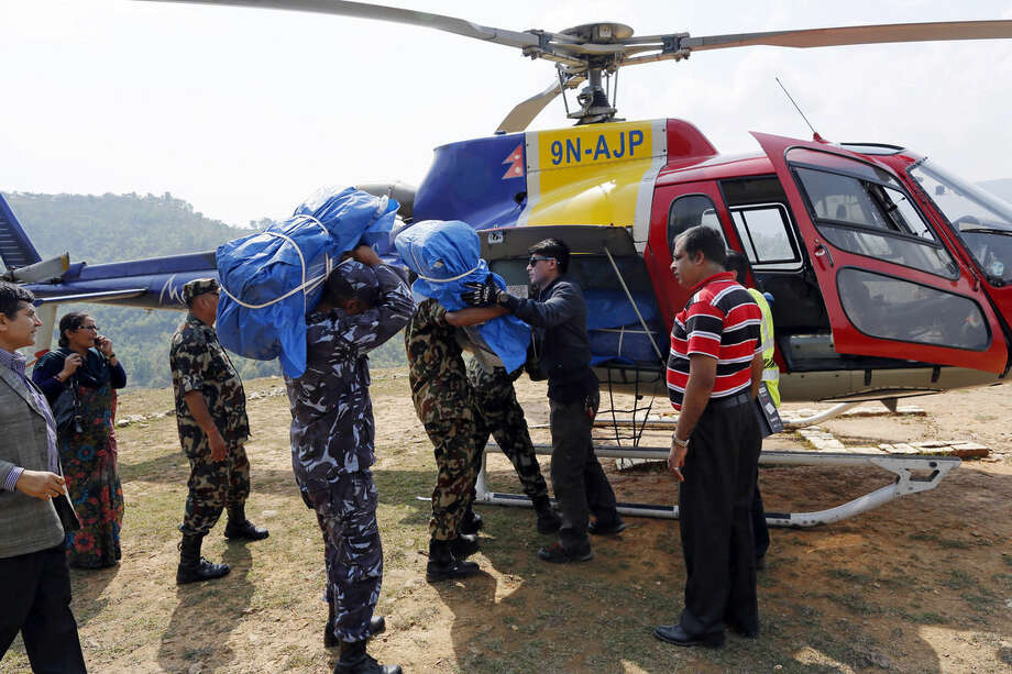 A helicopter is loaded with supplies at a relief staging area of landing zone near Saturday's massive earthquake's epicenter in the town of Gorkha, Nepal, Tuesday, April 28, 2015. Preparing to make a push into the most isolated parts of quake-devastated Nepal, soldiers on Tuesday were readying food, water and other emergency supplies to be loaded onto helicopters in this small town near the earthquake's epicenter. (AP Photo/Wally Santana)