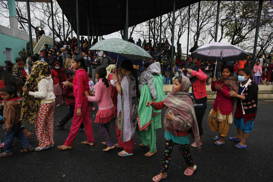 Nepalese victims of an earthquake stand in a queue to receive food in Kathmandu, Tuesday, April 28, 2015. A massive earthquake shook Nepal's capital and the densely populated Kathmandu valley on Saturday leaving hundreds of thousands of people living in the open without clean water or sanitation. (AP Photo/Niranjan Shrestha)