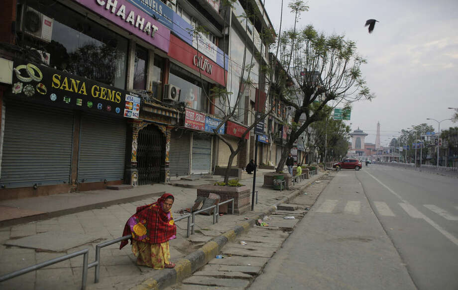 A Nepalese woman sits on a roadside in front of closed market in Kathmandu, Nepal, Tuesday, April 28, 2015. A strong earthquake shook Nepal's capital and the densely populated Kathmandu valley on Saturday. (AP Photo/Altaf Qadri)