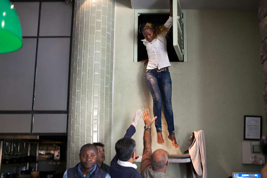 In this Sept. 21, 2013 photo provided by the New York Times, part of Tyler Hicks' Pulitzer Prize-winning portfolio, a woman leaps from a vent at a sushi restaurant at the Westgate Mall in Nairobi, Kenya, after a group of armed men attacked the upscale shopping mall in Nairobi. Hicks was awarded the 2014 Pulitzer Prize for breaking news photography, it was announced Monday, April 14, 2014, in New York. (AP Photo/The New York Times, Tyler Hicks)