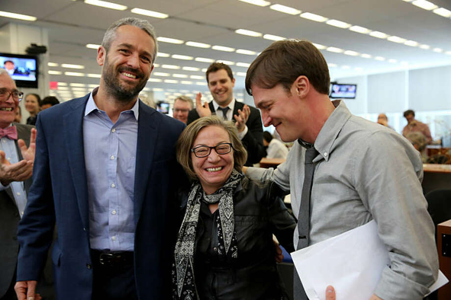 In this photo provided by The New York Times, Michele McNally, center, director of photography and assistant managing editor of The New York Times, is flanked by photographers Tyler Hicks, left, and Josh Haner after it was announced in the New York newsroom that Hicks and Haner had won Pulitzer Prizes for their work, Monday, April 14, 2014. Hicks won the 2014 Pulitzer Prize in breaking news photography for his coverage of a terrorist attack at an upscale mall in Nairobi, Kenya, that left more than 60 people dead. Haner was awarded the Pulitzer in feature photography for his images of the slow and painful recovery process for a survivor of the Boston Marathon bombing. (AP Photo/The New York Times, Richard Perry)