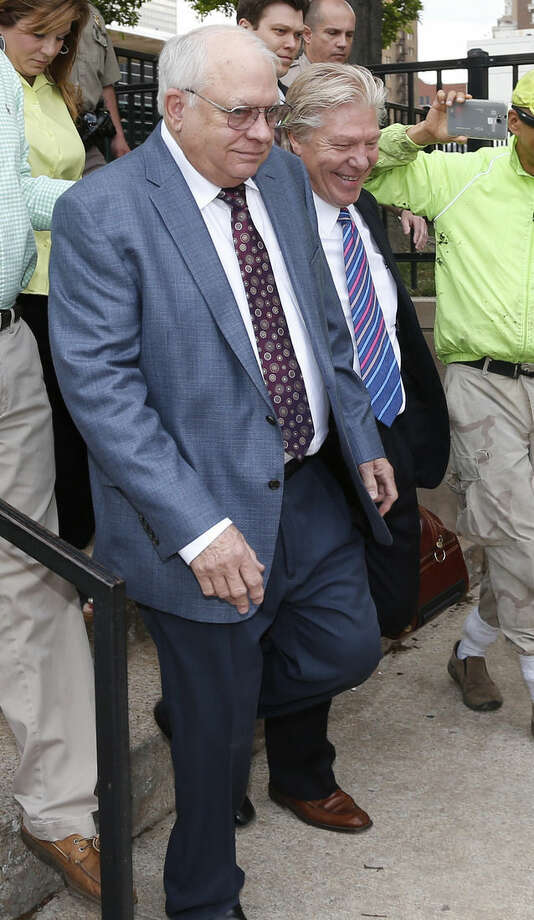 FILE - In this Tuesday, April 21, 2015 file photo, Robert Bates, left, leaves his arraignment with attorney Clark Brewster, right, in Tulsa, Okla. Bates, a 73-year-old Tulsa County reserve deputy who fatally shot a suspect who was pinned down by officers, is facing a second-degree manslaughter charge. (AP Photo/Sue Ogrocki)