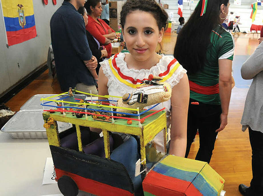 All Saints School 6th grader Sophia Ochoa representing Columbia with a tradional bus she made at the school's International Night. Hour photo/Matthew Vinci
