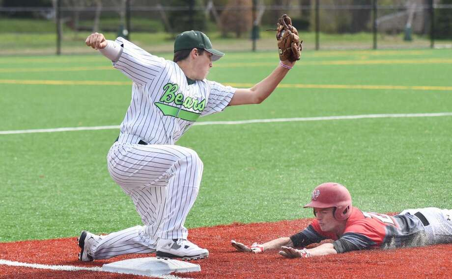 New Canaan's Thomas Reynolds, right, slides under the tag of Norwalk third baseman Tommy Benincaso during the first inning of Monday's FCIAC baseball game in Norwalk. The host Bears won, 5-0.