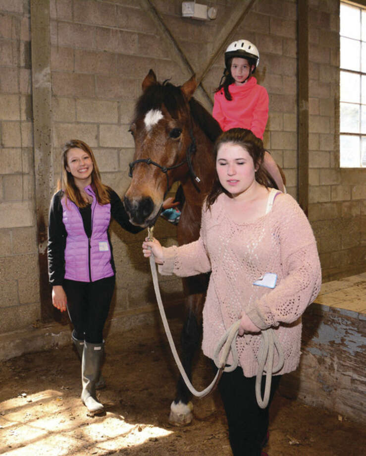 Volunteers Carly Hohorst, left, and Cayla Noble, right, lead one of the ponies with rider Jordan Silva during the 2015 Pony Rides for Jessica Rekos fundraiser, started by Norwalk native Montana Calloway. The event will be held again this year, Sunday, May 1 at the Second Company Governor's Horse Guard in Newtown, Conn.