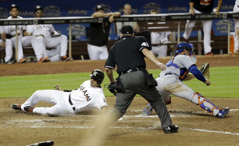 Miami Marlins' Martin Prado, left, slides safely into home plate on a base hit by teammate Michael Morse as New York Mets catcher Anthony Recker (20) awaits the throw in the eighth inning of a baseball game, Tuesday, April 28, 2015, in Miami. The Marlins won 4-3. (AP Photo/Alan Diaz)