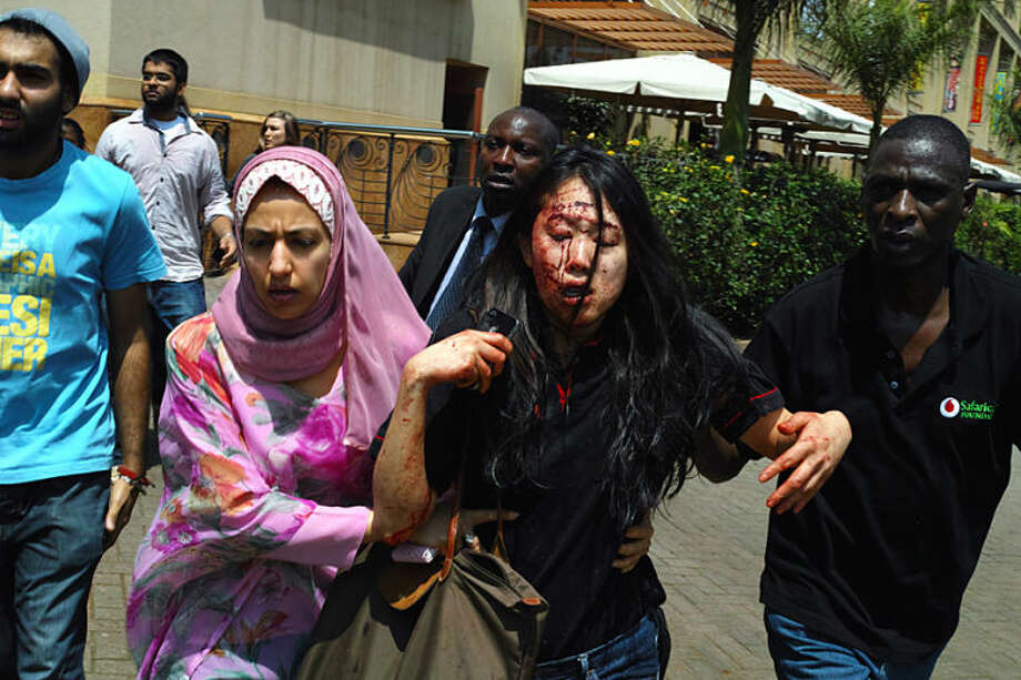 In this Sept. 21, 2013 photo provided by the New York Times, part of Tyler Hicks' Pulitzer Prize-winning portfolio, people assist injured shoppers while authorities search for gunmen at the Westgate Mall in Nairobi, Kenya, after a group of armed men attacked the upscale shopping mall in Nairobi. Hicks was awarded the 2014 Pulitzer Prize for breaking news photography, it was announced Monday, April 14, 2014, in New York. (AP Photo/The New York Times, Tyler Hicks)
