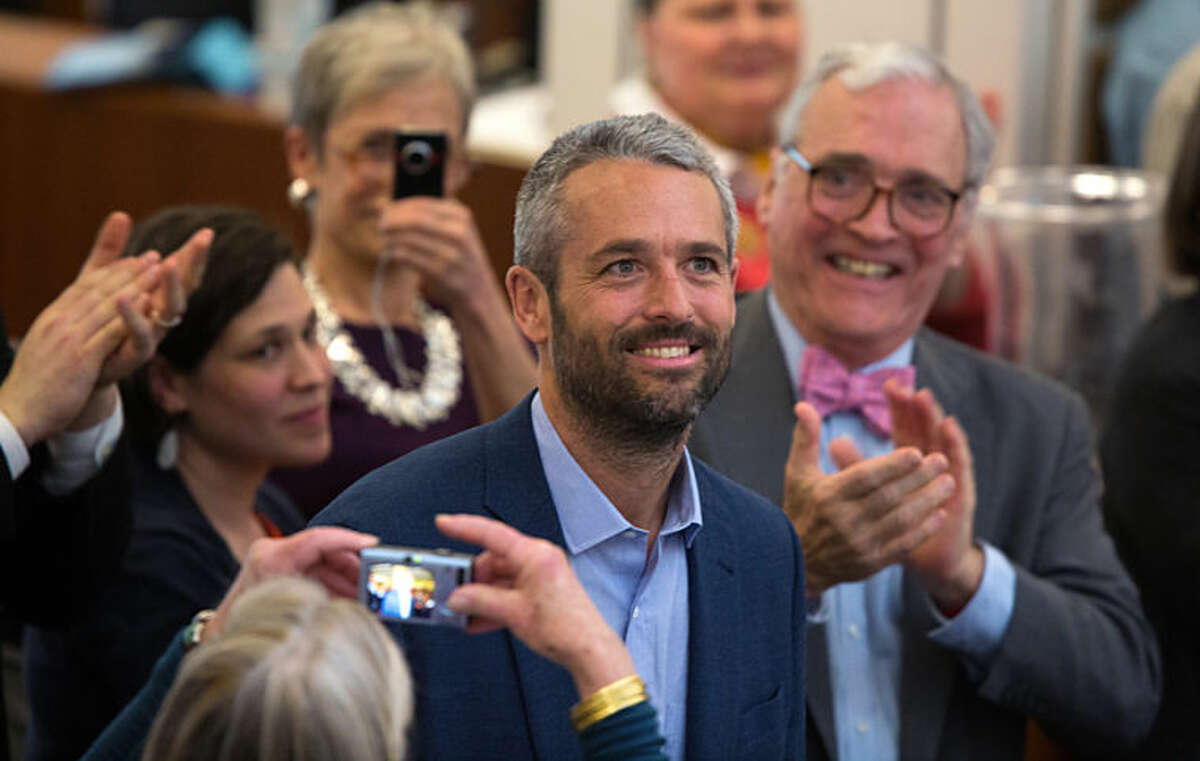 In this photo provided by The New York Times, photographer Tyler Hicks of The New York Times, center, is applauded by his colleagues in the newsroom after it was announced he won the Pulitzer Prize for breaking news photography, in New York, Monday, April 14, 2014. Hicks won the Pulitzer for his coverage of a terrorist attack at an upscale mall in Nairobi, Kenya, that left more than 60 people dead. (AP Photo/The New York Times, Ruth Fremson)