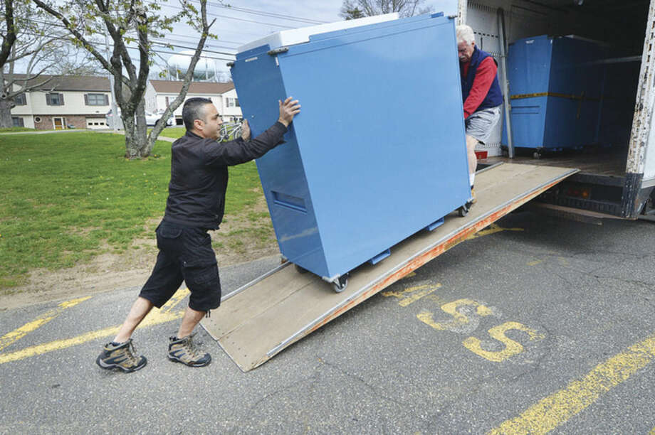 Angelo Greco and Rich Bartlett roll a cabinet from a truck containing balllots, tabulators and voting items into the polling place at Nathan Hale School to be set up for Tuesdays primary voting in Norwalk Conn. April 25 2016