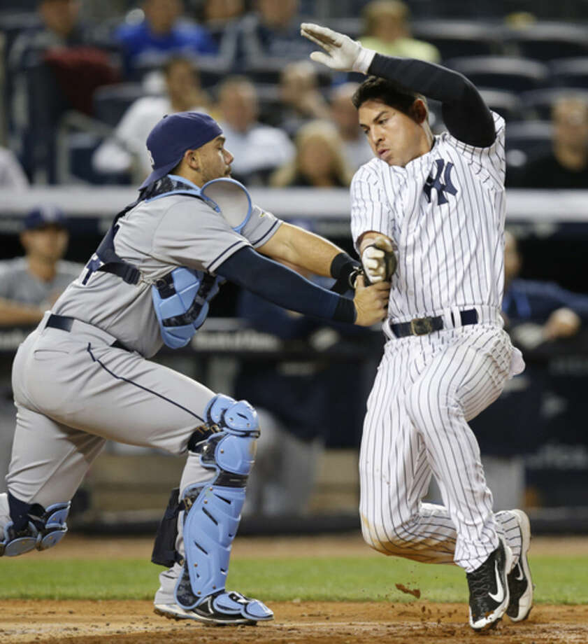Tampa Bay Rays catcher Rene Rivera (44) tags out New York Yankees Jacoby Ellsbury at the plate after Ellsbury tried to score on a seventh-inning fielder's choice that Brett Gardner hit into during a baseball game at Yankee Stadium in New York, Tuesday, April 28, 2015. (AP Photo/Kathy Willens)