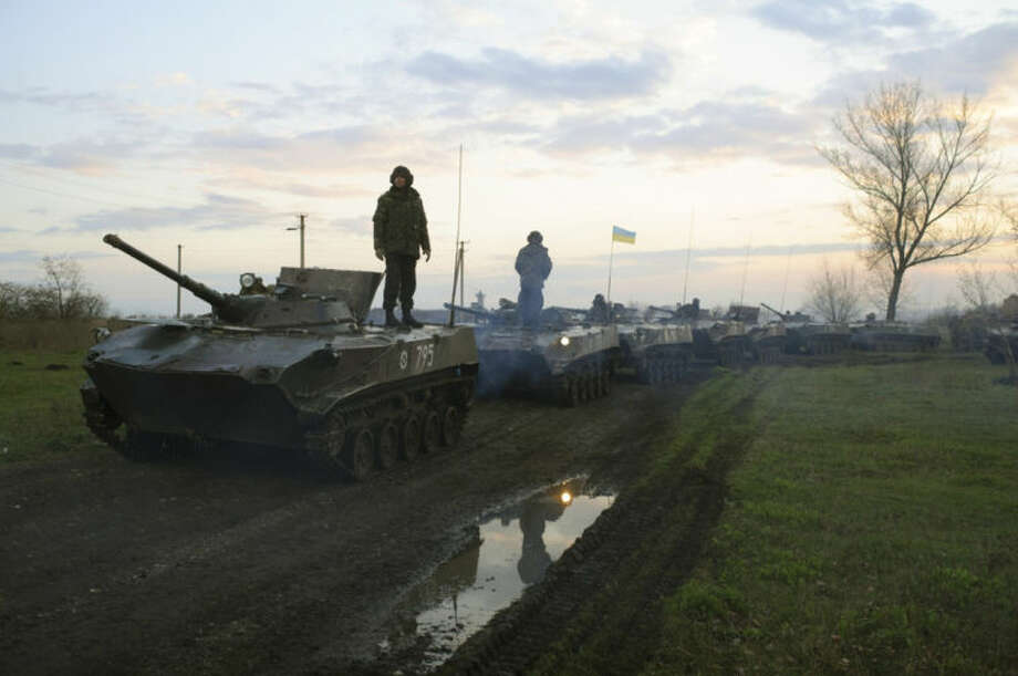 In this photo taken on Monday, April 14, 2014, Ukrainian soldiers stand on military vehicles with Ukrainian national flags in a field about 70 kilometers (44 miles) from the eastern Ukrainian town of Slovyansk, where the Ukrainian regional administration building was seized by pro-Russian activists. A deadline set by the Ukrainian government for pro-Russian gunmen to leave government buildings in eastern Ukraine and surrender weapons passed without incident early Monday, with no immediate sign of any action to liberate any seized buildings. (AP Photo/Russian Reporter magazine, Maxim Dondyuk) MAGAZINES OUT EDITORIAL USE ONLY