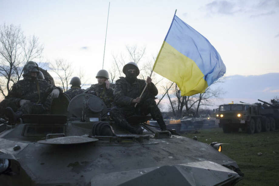 In this photo taken on Monday, April 14, 2014, Ukrainian soldiers sit on top of military vehicles with a Ukrainian national flag in a field about 70 kilometers (44 miles) from the eastern Ukrainian town of Slovyansk, where the Ukrainian regional administration building was seized by pro-Russian activists. A deadline set by the Ukrainian government for pro-Russian gunmen to leave government buildings in eastern Ukraine and surrender weapons passed without incident early Monday, with no immediate sign of any action to liberate any seized buildings. (AP Photo/Russian Reporter magazine, Maxim Dondyuk) MAGAZINES OUT EDITORIAL USE ONLY