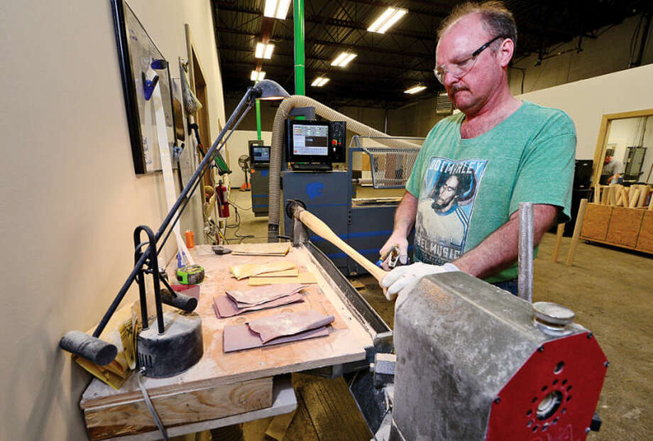 Hour photo / Erik Trautmann Dale Wheeler works in the new production facility for the local baseball bat company, Tucci Lumber, now located on Wilson Ave.