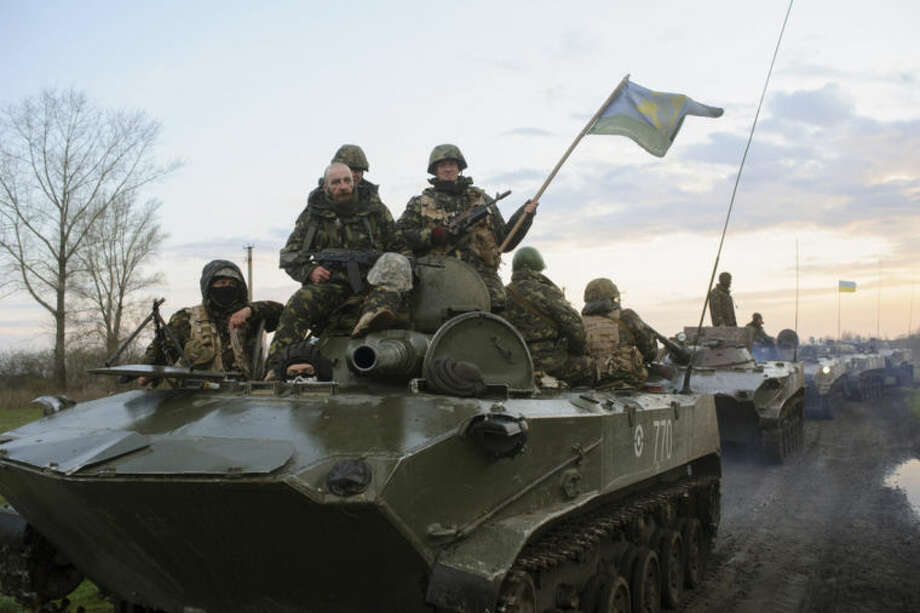 In this photo taken on Monday, April 14, 2014, Ukrainian soldiers sit on top of military vehicles with Ukrainian national flags in a field about 70 kilometers (44 miles) from the eastern Ukrainian town of Slovyansk, where the Ukrainian regional administration building was seized by pro-Russian activists. A deadline set by the Ukrainian government for pro-Russian gunmen to leave government buildings in eastern Ukraine and surrender weapons passed without incident early Monday, with no immediate sign of any action to liberate any seized buildings.(AP Photo/Russian Reporter magazine, Maxim Dondyuk) MAGAZINES OUT EDITORIAL USE ONLY
