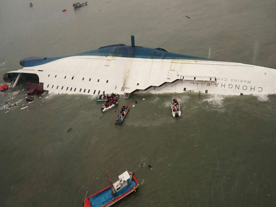 In this photo released by South Korea Coast Guard via Yonhap News Agency, South Korean rescue team boats and fishing boats try to rescue passengers of a ferry sinking off South Korea's southern coast, in the water off the southern coast near Jindo, south of Seoul, Wednesday, April 16, 2014. Nearly 300 people were still missing Wednesday several hours after a ferry carrying 459, most of them high school students, sank in cold waters off South Korea's southern coast. (AP Photo/South Korea Coast Guard via Yonhap) KOREA OUT