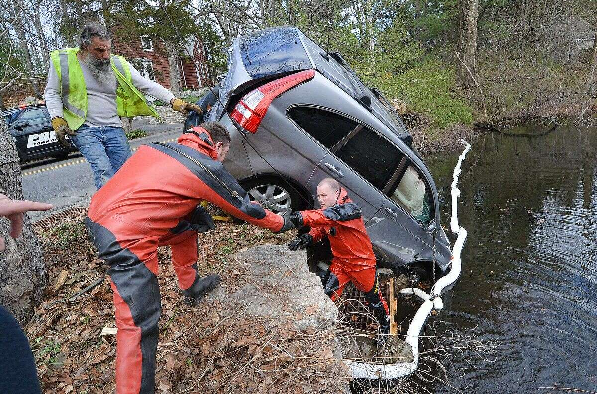 Wilton Firefighters and Dive Team members Bill Wilson and Mike Pryor help to secure a tow rig from a truck on a Honda CRV after a two-car accident sent the Honda CRV over the wall into Horseshoe pond on Monday, the driver was already out of the vehicle when emergency personnel arrived. Horeshoe Road was closed in both directions for over an hour until the car was pulled from the water. The driver of the other car, a Toyota sedan, and the driver of the Honda were transported to Norwalk Hospital.