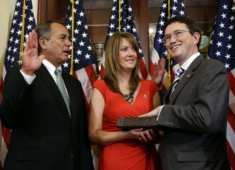 FILE - In this Nov. 13, 2012 file photo, House Speaker John Boehner of Ohio, left, administers the House oath during a mock swearing in ceremony for Rep. Thomas Massie, R-Ky., right, with his wife Rhonda Massie, on Capitol Hill in Washington. As he began his first re-election run in early 2013, Massis had no trouble raising money from the business community. Through March, he reported $46,000 rolling in from tobacco, trucking, health care and other business groups. And then came 2015. For the first three months of this year, that figure is down to zero. The sole donation he listed from political action committees _ organizations representing business, labor or ideological interests _ is $1,000 from the conservative Eagle Forum. (AP Photo/Alex Brandon, File)