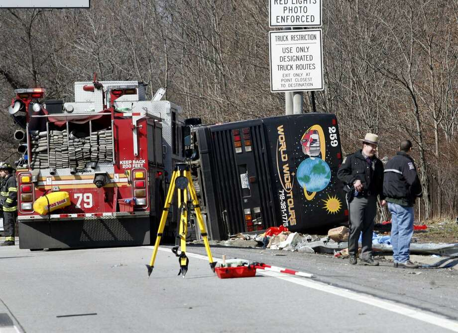 Emergency personnel investigate the scene of a bus crash on Interstate-95 in the Bronx borough of New York Saturday, March 12, 2011. Thirteen people died when the bus, returning to New York from a casino in Connecticut, flipped onto its side and was sliced in half by the support pole for a large sign. The U.S. DOT proposed new safety standards for buses.