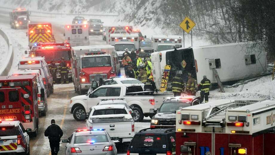 Emergency responders work at the scene of a tour bus rollover on Interstate 95 northbound in the area of exit 61 on Monday, February 8, 2016 in Madison, Conn. The bus was traveling from New York City to the Mohegan Sun casino in Uncasville, Conn. The U.S. DOT proposed new safety standards for buses.