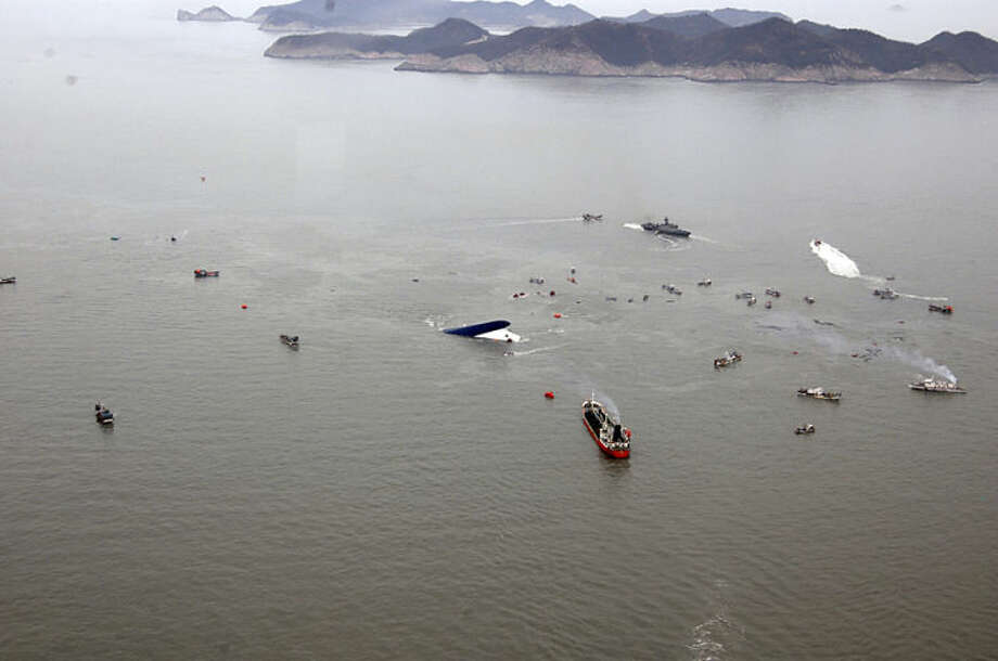 In this photo released by South Korean Navy via Yonhap News Agency, South Korean rescue team boats and fishing boats try to rescue passengers of a ferry sinking off South Korea's southern coast, in the water off the southern coast near Jindo, south of Seoul, Wednesday, April 16, 2014. Nearly 300 people were still missing Wednesday several hours after a ferry carrying 477, most of them high school students, sank in cold waters off South Korea's southern coast. (AP Photo/South Korean Navy via Yonhap) KOREA OUT