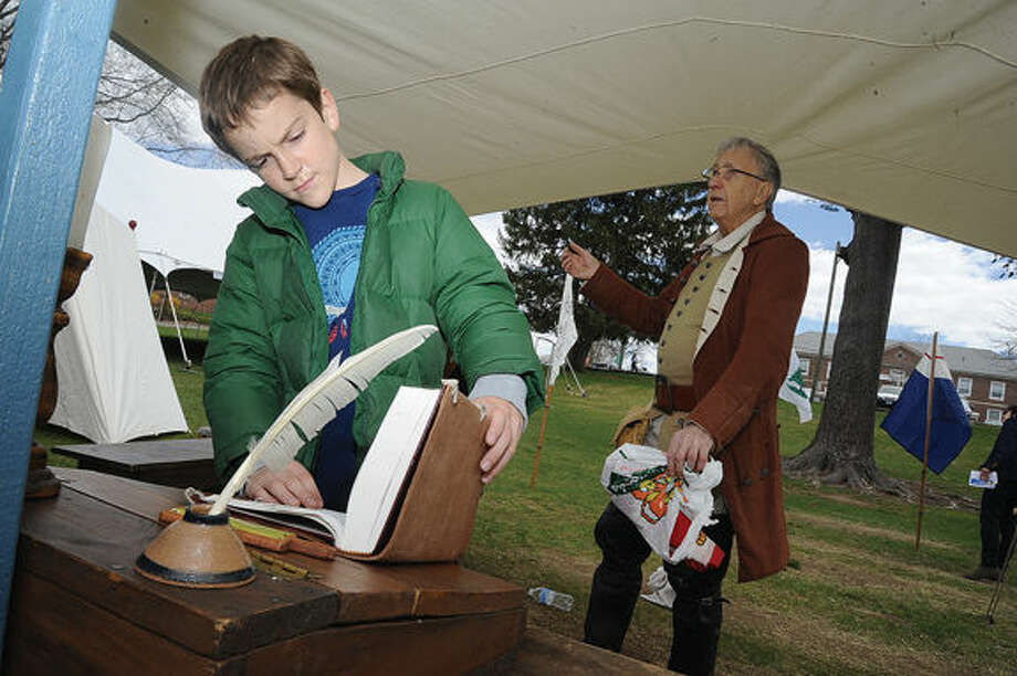 10 year old Julian Fiore looks at artifacts in a Revolutionary encampment set up by the Connecticut Sons of the American Revolution Sunday as the Town of Westport celebrated Minute Man Day. Hour photo/Matthew Vinci