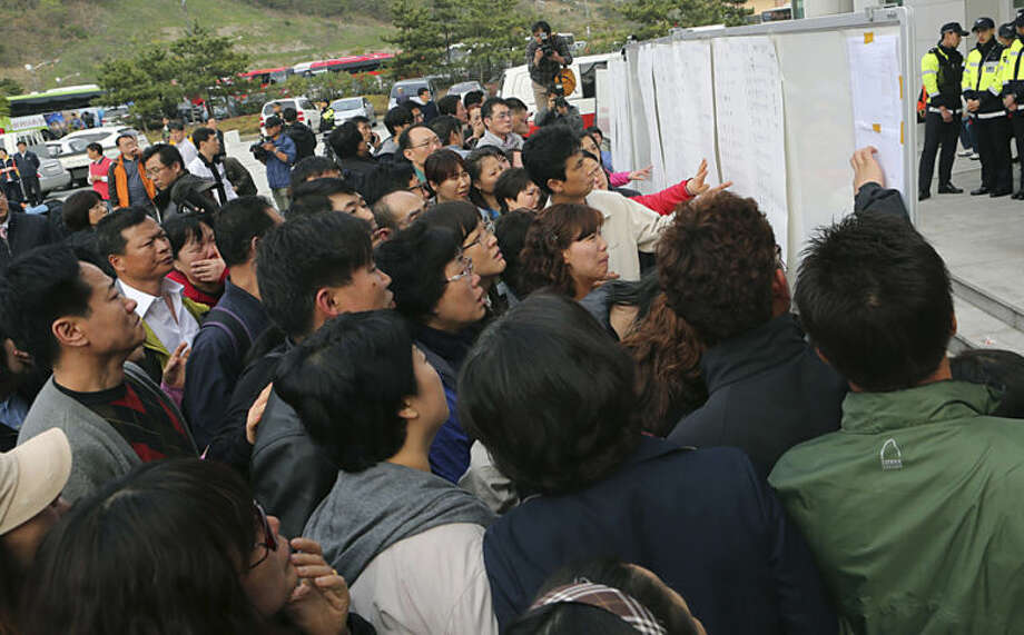 Parents and relatives check the rescued passengers lists at a gymnasium in Jindo, south of Seoul, Wednesday, April 16, 2014. A multi-story ferry carrying 459 people, mostly high school students on an overnight trip to a tourist island, sank off South Korea's southern coast Wednesday, leaving nearly 300 people missing despite a frantic, hours-long rescue by ships and helicopters. At least two people were confirmed dead and seven injured. (AP Photo/Yonhap) KOREA OUT