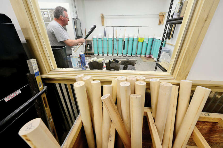 Hour photo / Erik Trautmann Walt Lagutko works in the dipping room in the new production facility of the local baseball bat company, Tucci Lumber, which is now located on Wilson Ave.