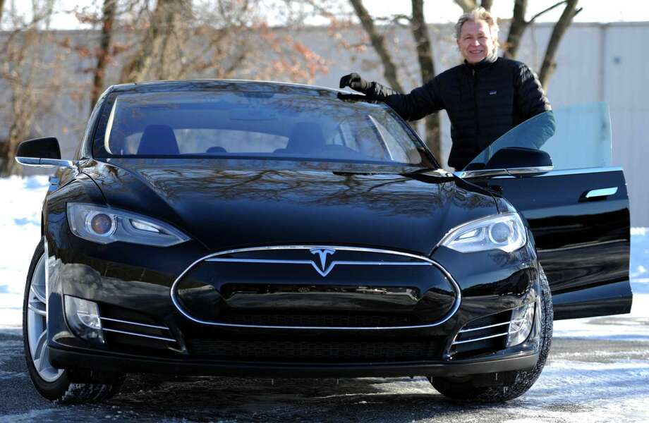 Roger Van Brussel, a Milford resident and business owner, stands in front of his new Tesla Model S 85 Thursday, Feb. 5, 2015, in Milford, Conn. Van Brussel had to leave the state to purchase the electric car but Connecticut is contemplating changing its laws so that Tesla can sell its cars here. Currently, only franchised car dealerships can sell cars in this state, not manufacturers.