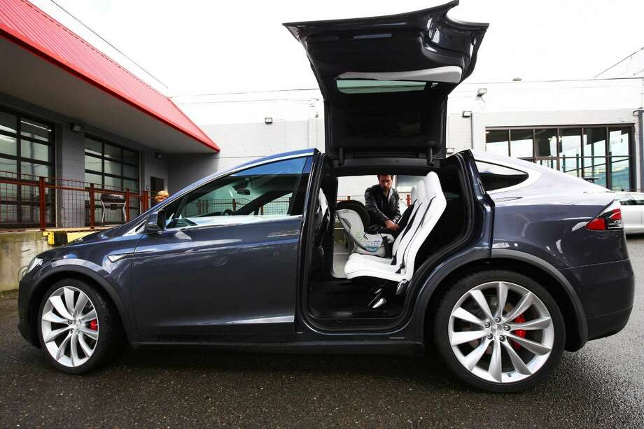 Tesla showed off its new Model X to customers at a private event at its Sodo service center, giving them the chance to get up close and personal with the car, Thursday, Feb. 3, 2016. Though the electric car's base model is set to start at $75,000, the first 1,000 Model Xs are fully-loaded signature series P90D versions that go for around $132,000. (Genna Martin, seattlepi.com)
