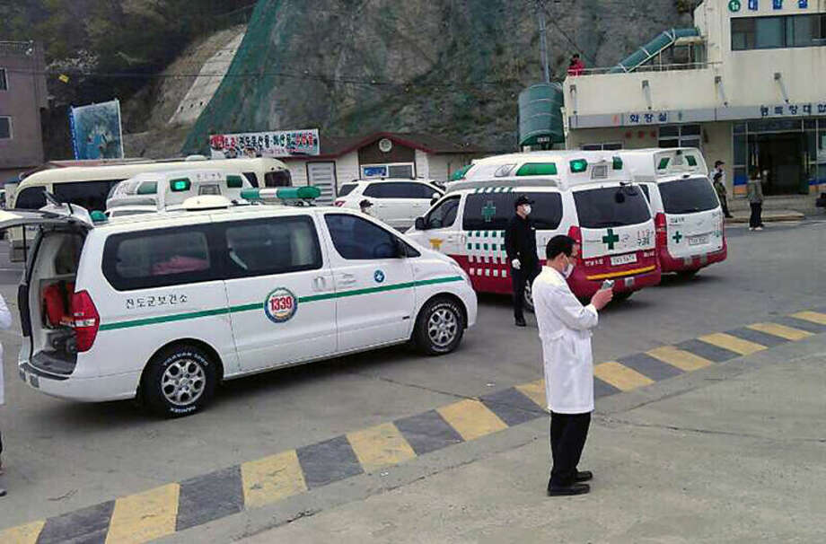 Ambulances wait for rescued passengers from a ferry sinking off South Korea's southern coast, at Jindo port in Jindo, south of Seoul, South Korea, Wednesday, April 16, 2014. Dozens of military boats and helicopters scrambled Wednesday to rescue more than 470 people, including 325 high school students on a school trip, after the ferry sank off South Korea's southern coast, officials said. (AP Photo/Yonhap) KOREA OUT