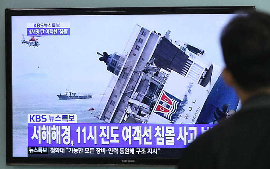 """A man watches a TV news program showing a sinking passenger ship, at Seoul Railway Station in Seoul, South Korea, Wednesday, April 16, 2014. The South Korean passenger ship carrying more than 470 people, including many high school students, is sinking off the country's southern coast Wednesday after sending a distress call, officials said. There are no immediate reports of causalities. The letters on the screen read """" A passenger ship sank at 11:00 AM."""" (AP Photo/Ahn Young-joon)"""