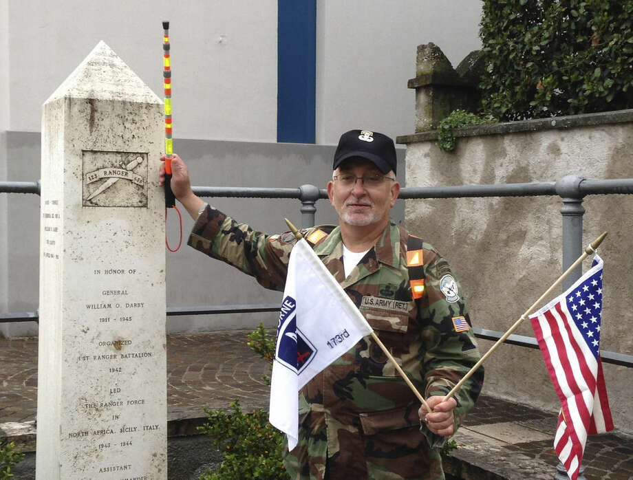 In this April 30, 2014 photo provided by Ben Appleby, Rick Tscherne poses with a memorial to Col. William O. Darby in Torbole, Italy. The former U.S. Army Ranger is organizing a 40-mile road march in northern Italy to commemorate the 70th anniversary of the deaths of Darby, a legendary World War II officer, and 25 of his soldiers on the same day. (Ben Appleby via AP)