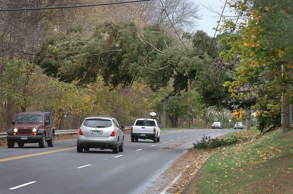 Hour Photo Alex von Kleydorff; Traffic along Rt 7 in Wilton passes under a giant fallen evergreen tree suspended by wires across the road.
