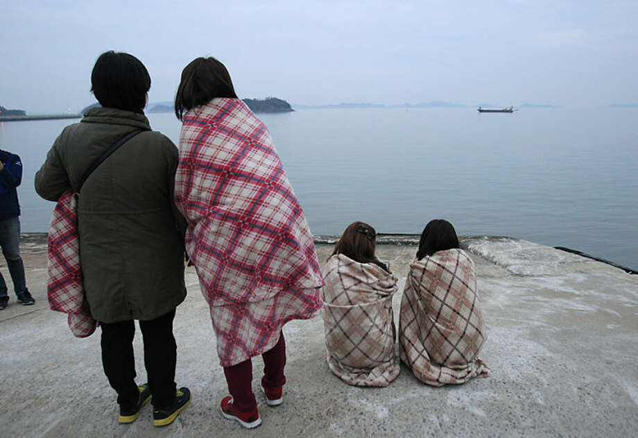 Relatives of passengers of a sunken ship wrapped in blankets look toward the sea at Jindo port, South Korea, Wednesday, April 16, 2014. The ferry carrying 459 people, mostly high school students on an overnight trip to a tourist island, sank off South Korea's southern coast on Wednesday, leaving nearly 300 people missing despite a frantic, hours-long rescue by dozens of ships and helicopters. (AP Photo/Ahn Young-joon)