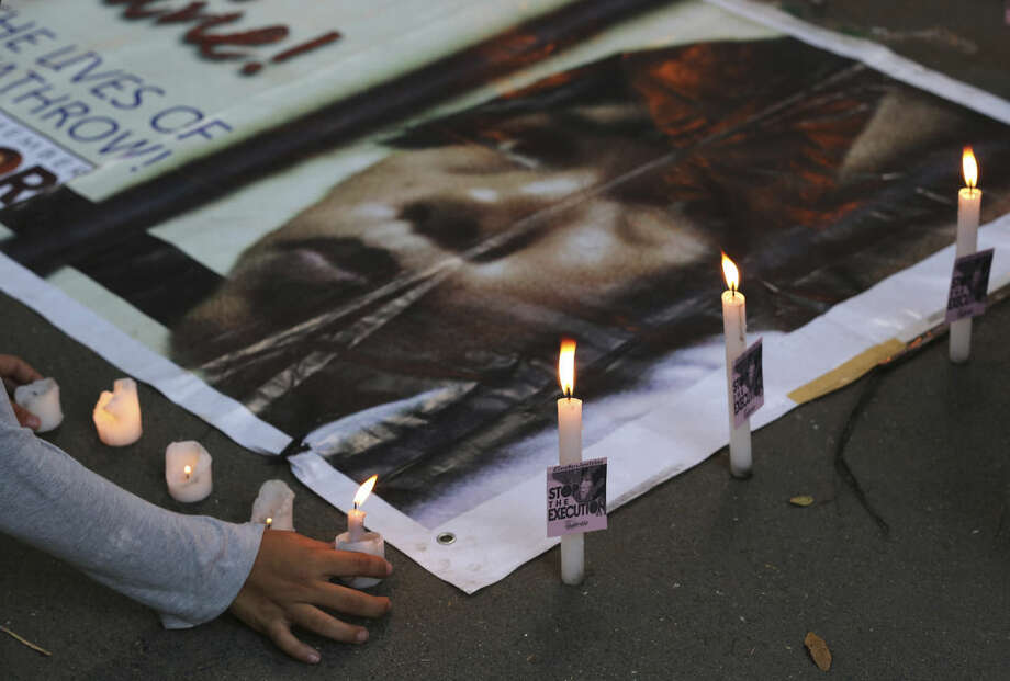 A Filipino protester lights a candle beside a picture of convicted Filipino drug trafficker Mary Jane Veloso as they call on the Indonesian government to spare her life during a rally outside the Indonesian Embassy in the financial district of Makati, south of Manila, Philippines on Sunday, April 26, 2015. Indonesia notified nine foreigners and an Indonesian convicted of drug trafficking that their executions will be carried out within days, ignoring appeals by the U.N. chief and foreign leaders to spare them. (AP Photo/Aaron Favila)