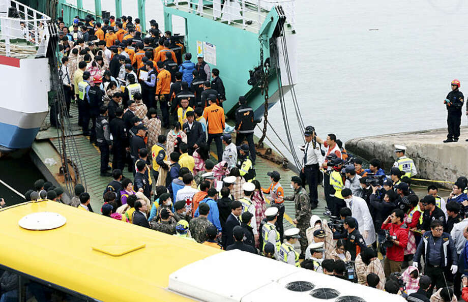 Rescued passengers are escorted by members of a rescue team upon their arrival at a port in Jindo, south of Seoul, South Korea, Wednesday, April 16, 2014. More than 100 people were still unaccounted Wednesday several hours after a ferry carrying 476, most of them high school students, sank in cold waters off South Korea's southern coast, killing at least two and injuring 14, officials said. (AP Photo/Yonhap, Park Chul-heung) KOREA OUT