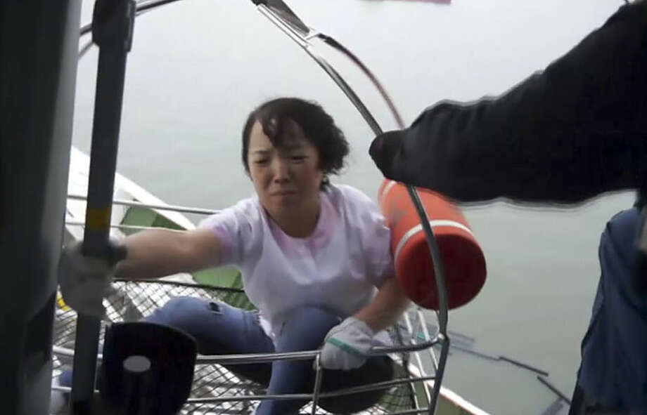 In this image made from video from South Korean Coast Guard, a passenger of a ferry sinking off South Korea's southern coast is rescued and hoisted onto a Coast Guard helicopter off the southern coast near Jindo, south of Seoul, Wednesday, April 16, 2014. Nearly 300 people were still missing Wednesday several hours after a ferry carrying 459, most of them high school students, sank in cold waters off South Korea's southern coast. (AP Photo/South Korean Coast Guard via AP Video)