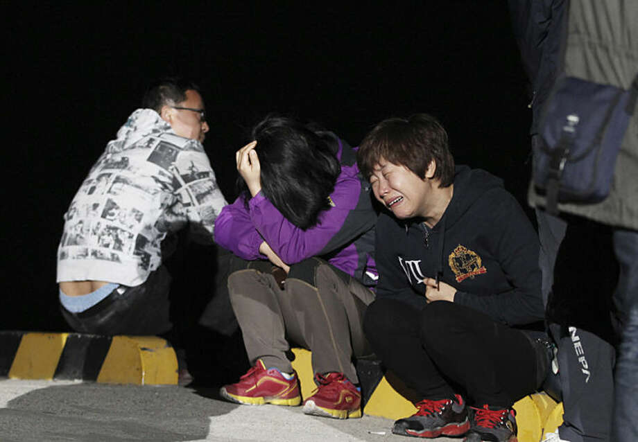 A relative weeps as she waits for missing passengers of a sunken ferry at Jindo port, South Korea, Wednesday, April 16, 2014. The ferry carrying 459 people, mostly high school students on an overnight trip to a tourist island, sank off South Korea's southern coast on Wednesday, leaving nearly 300 people missing despite a frantic, hours-long rescue by dozens of ships and helicopters. (AP Photo/Ahn Young-joon)