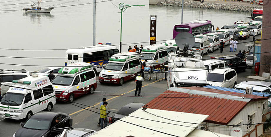 Ambulances wait for rescued passengers from a ferry that sank off South Korea's southern coast, at a port in Jindo, south of Seoul, South Korea, Wednesday, April 16, 2014. More than 100 people were still unaccounted Wednesday several hours after a ferry carrying 476, most of them high school students, sank in cold waters off South Korea's southern coast, killing at least two and injuring 14, officials said. (AP Photo/Yonhap, Park Chul-heung) KOREA OUT