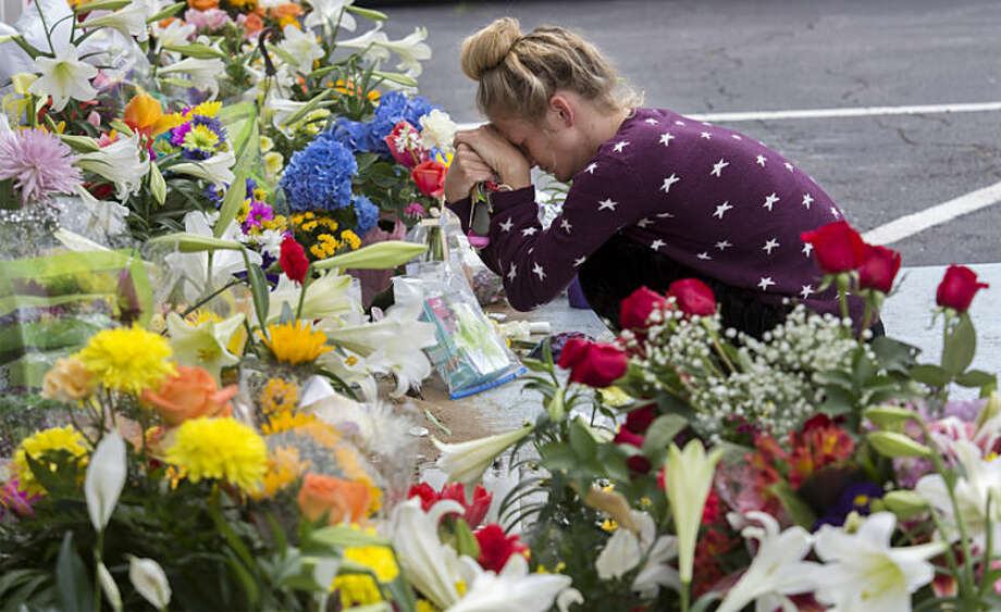 Julia West of Virginia Beach as she kneels in front of Beach Pharmacy on Laskin Road in Virginia Beach Tuesday, April 15, 2014 after she and her mom, Gerrie West placed flowers with others in front of the pharmacy where owner David Kilgore was shot and later died during an attempted robbery Monday, April 14, 2014. (AP Photo/The Virginian-Pilot, Bill Tiernan)